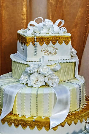 Wedding cake specially decorated with white ribbons and edible flowers  photo