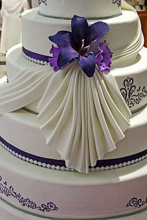 Wedding cake specially decorated with edible purple flowers and ribbons