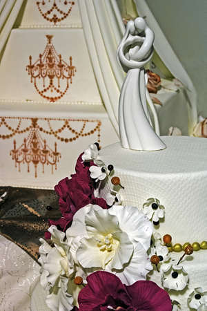 tiered: Wedding cake specially decorated with edible flowers and statue symbolizing love