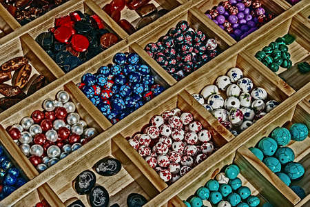 Colored beads with different shapes, presented in a wooden box divided