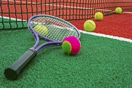 Ball and tennis racket arranged around the net on a synthetic field  photo