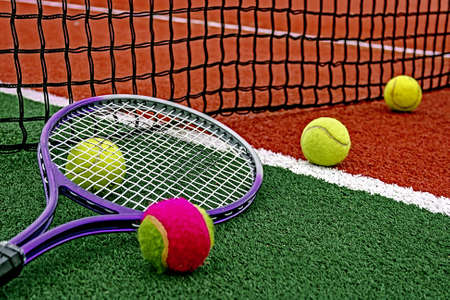 lawn tennis: Ball and tennis racket arranged around the net on a synthetic field