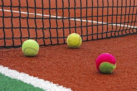 Tennis balls placed around the net on a synthetic field  photo