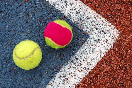 Tennis colored balls placed in the corner of a synthetic field  photo