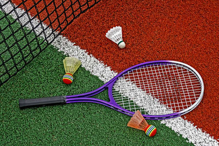 Shuttlecock and badminton racket arranged around the net on a synthetic field  photo