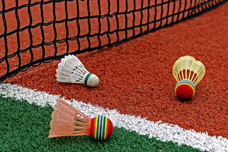 Badminton shuttlecocks placed around the net on a synthetic field  photo