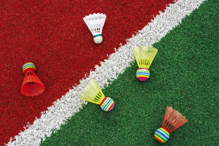 Badminton colored shuttlecocks, placed on synthetic field  photo