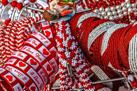 Bracelets with love logos, beads and necklaces in white and red, displayed on a stand Symbolizes the arrival of spring