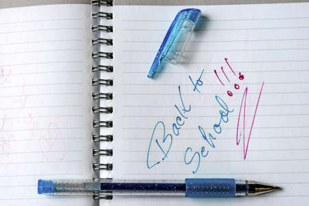 Notebook with metal spiral and pencil, opened at one page that says  ,,back to school   in colors cyan and magenta  photo