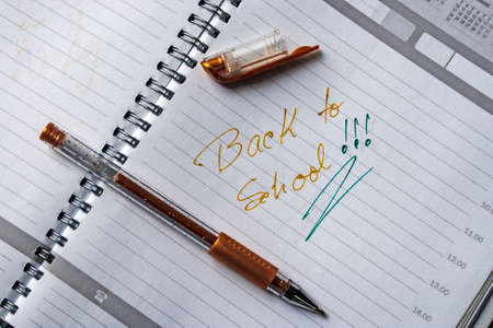 Notebook with metal spiral and pencil, opened at one page that says  BACK TO SCHOOL in colors green and brown  photo