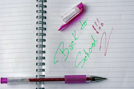 Notebook with metal spiral and pencil, opened at one page that says  BACK TO SCHOOL in colors purple and green  photo