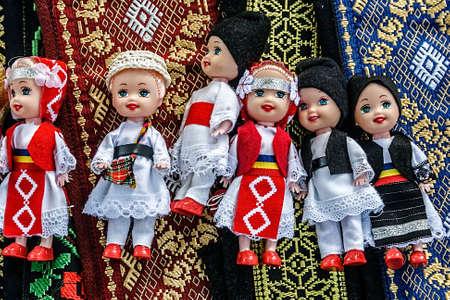 Bebekler geleneksel Romen halk kostümleri giymiş ve işlemeli malzemeler üzerinde ayarlama