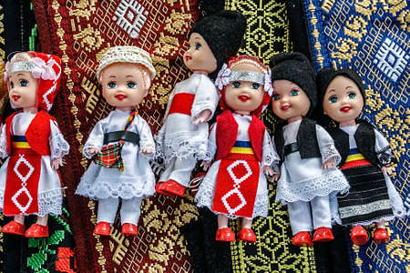 Dolls dressed in traditional Romanian folk costumes and set over embroidered materials