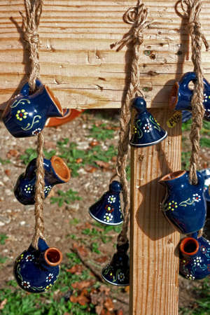 Pitchers and ceramic bells, hanging with strings on a plank of wood  Decorations specific for Korond area, Transylvania, Romania