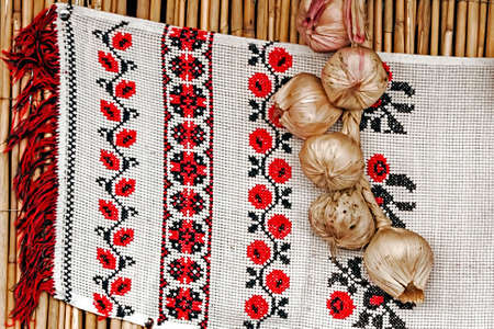 Romanian decorative embroidery, sitting on a reed wall, along with a bunch of garlic  photo