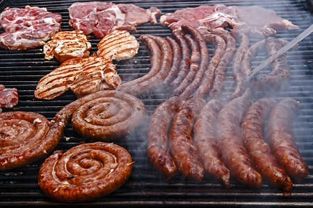 Sausages and pork fried meat, placed on the grill. photo