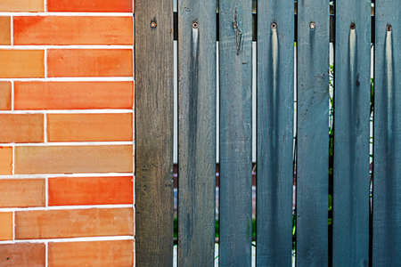Fence plated with ornamental stone and planks. photo