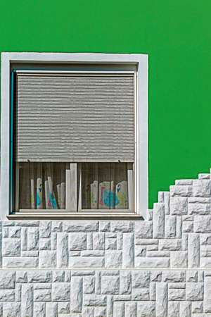 iron curtains: Ornamental facade of house with window, painted in green and white stone at the base. Stock Photo