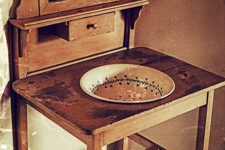 Old furniture for washing their hands, composed of a ceramic bowl decorated and wooden table. Used in rural areas from Vojvodina, Serbia. Image digitally manipulated in the form of old photos. photo
