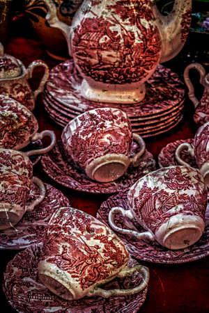 Old ceramic cups with red paintings applied. Image digitally manipulated as one old photo. photo
