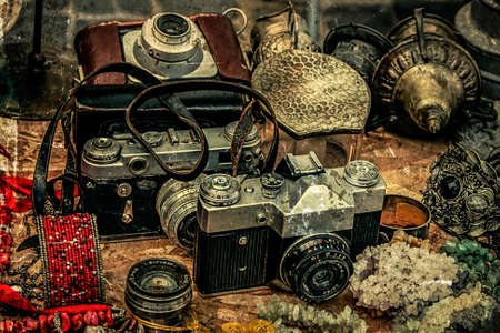antique table: Old postcards with vintage look at one fair. Old photo cameras and different antiques.