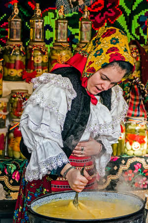 Young woman dressed in traditional costume from Maramures, Romania, mixed polenta in a large pot on a background with traditional embroidery.Street winter Fair in Timisoara, Romania, December 2014.