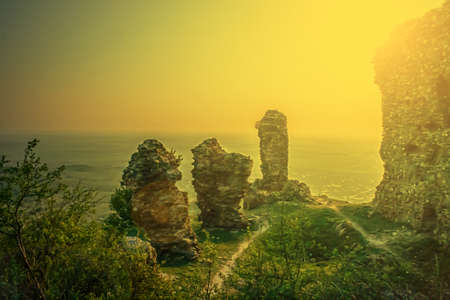 Old photo with ruins fortress Siria located in district Arad, Romania. Image digitally manipulated in the form of old photos. Sunset light. photo
