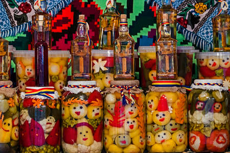 Jars with pickles and bottles with alcohol, traditional from area Maramures, Romania, displayed on a background with traditional embroidery. Фото со стока