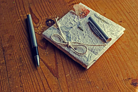 old diary: Old diary memories with a pen on a wooden table. Vintage processing.