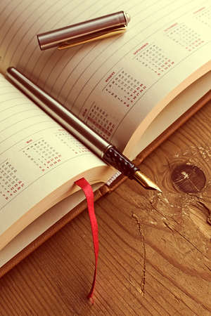 open diary: Open diary with one fountain pen in it, placed on a wood table. Vintage processing.