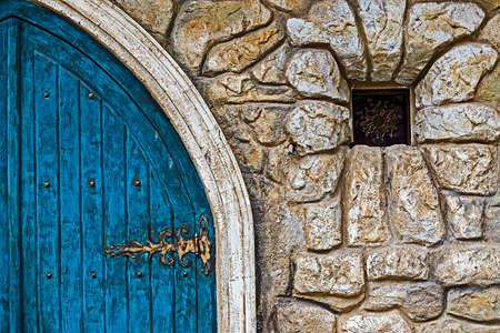 overbuilding: Muro di pietra texture di sfondo con l'antica porta blu al castello e piccola finestra.