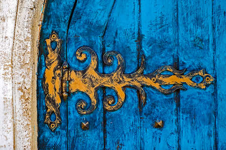 overbuilding: Stone wall texture background with ancient blue door.
