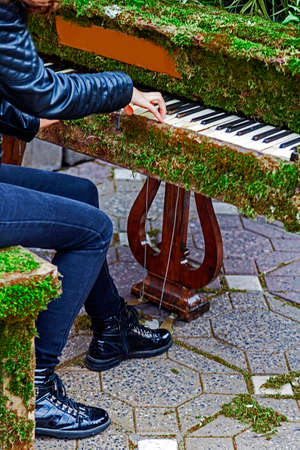 rocker girl: Rocker girl singing at one piano decorated with flowers and moss grass.