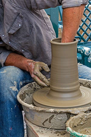 shaping: Young artist shaping a clay pot with hands.
