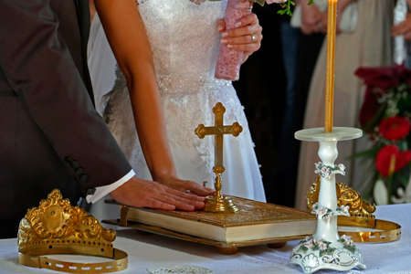 bible altar: Groom and bride swear with hand on bible faith in marriage in a church.