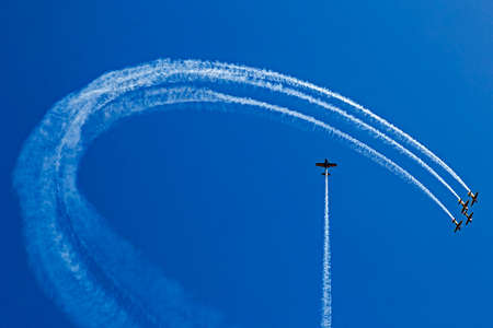 aerobatic: Drawings of smoke in the sky made from airplanes at a airshow demonstration.