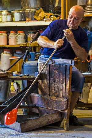 MURANO, ITALY - AUGUST, 5: Glassworker in action in the Murano glass factory on August 5, 2015. Редакционное