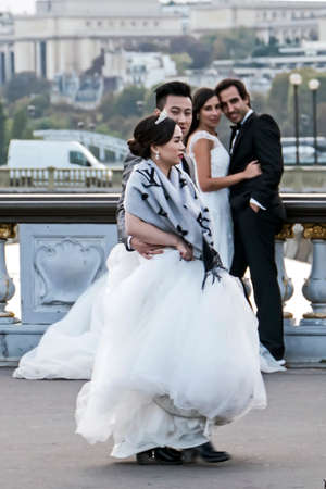 intersect: PARIS, FRANCE - OCTOBER 10, 2015: Street photography. Two couples of newlyweds, coming from two continents, which intersect on Alexander bridge in Paris.