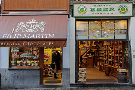 specific: BRUSSELS, BELGIUM - OCTOBER 15, 2015: Street photography with two shops in Bruxelles which represent the Belgian specific. Chocolate and beer traditional.