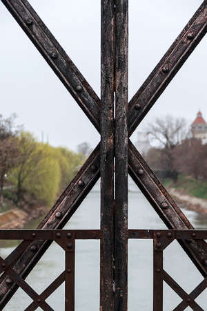 fastened: Structure of rusty metal beams fastened with rivets, part of an old bridge. Stock Photo