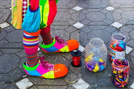 clowning: TIMISOARA, ROMANIA - MARCH 29, 2015: Body part of a clown and jars with colorful balloons.