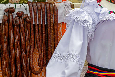 specific: Romanian traditional sausages hanging on a fence, in a setting with specific costumes from Maramures, Romania.
