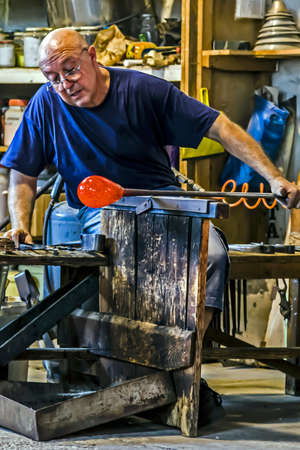 Murano: MURANO, ITALY - AUGUST 5, 2015: Glassworker in action in the Murano glass factory on August 5, 2015. Editorial