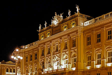 Night view with architectural detail of facade at Lloyd Triestino palace in Unity of Italy Square.Trieste, Italy.
