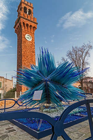 simone: MURANO, ITALY - JANUARY 25, 2016: A modern sculpture of Murano glass designed by Master glassmaker and Designer Simone Cenedese in front of the old bell tower of San Giacomo on Murano island, Venice.