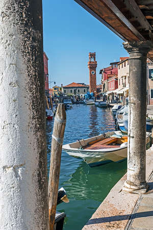 Murano: View of a channel at Murano island in Venice, Italy, with clock tower and Cometa glass monument in background.