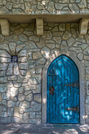 overbuilding: Stone wall texture background with ancient blue door to the castle and small window.