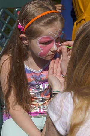 maquillaje infantil: TIMISOARA, Rumania - MAI 07, 2016: Taller para niños enfrentan la pintura en un parque en Timisoara, Rumanía.