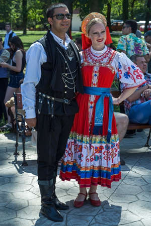 turkish man: ROMANIA, TIMISOARA - JULY 12, 2015: Turkish man and young Ukrainian girl, in traditional specific costumes, attended at a international folk dance festival,during ,,International Festival of hearts