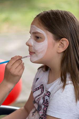 maquillaje infantil: TIMISOARA, Rumania - JUNIO 01, 2016: Taller con pintura de la cara para los niños, en un parque en Timisoara, Rumanía. Día Internacional de los niños.